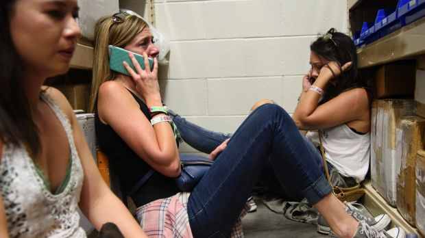Women make phone calls while taking shelter inside the Sands Corporation plane hangar during the Las Vegas shooting.