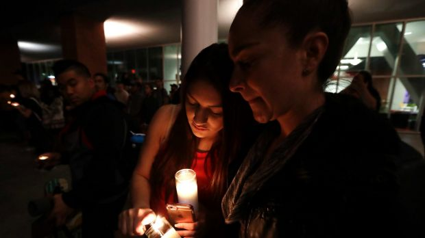 Virginia, right, and Natalie Ramos light candles at a vigil in Las Vegas.