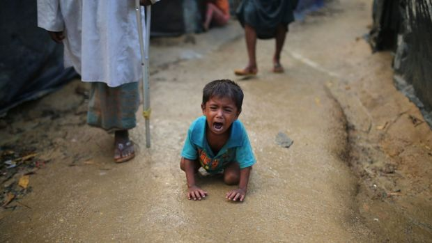 A Rohingya child cries on the ground at a makeshift refugee camp in Bangladesh. Children have given harrowing accounts ...