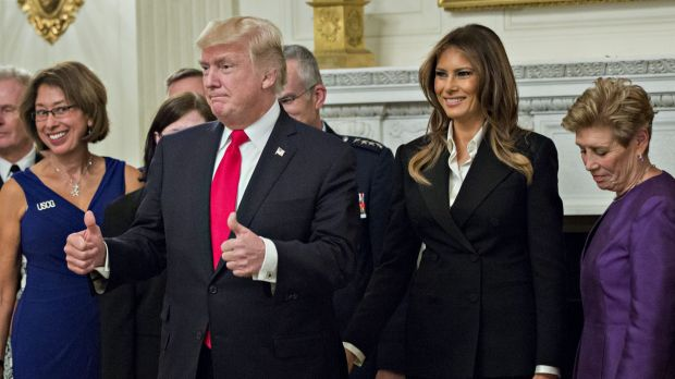 US President Donald Trump gives a thumbs up next to first lady Melania Trump during an official photograph with senior ...