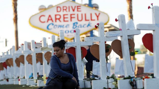 Cece Navarrette sits near a cross for her cousin, Bailey Schweitzer, who was among those killed during the mass shooting ...