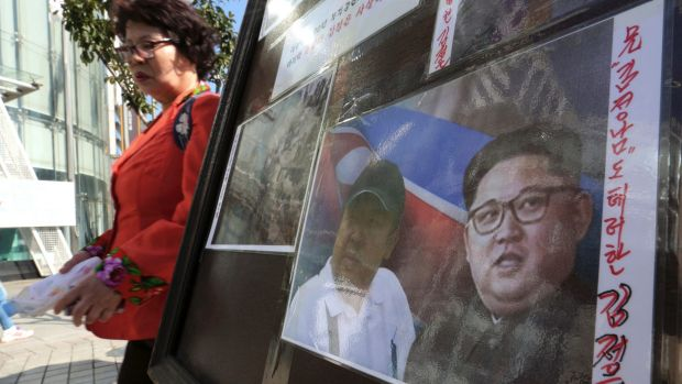 A sign shows images of North Korean leader Kim Jong-un, right, and his older brother Kim Jong-nam during a campaign to ...