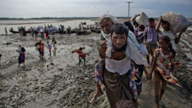 A Rohingya Muslim man from Myanmar carries an elderly woman after they crossed the border into Bangladesh from Myanmar ...