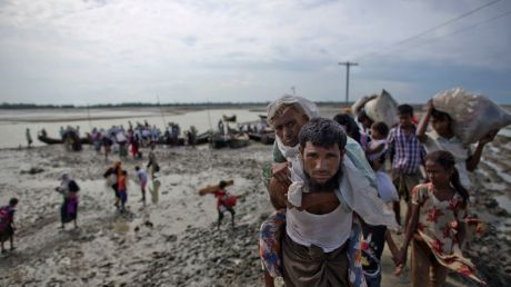 Rohingya Muslim man from Myanmar carries an elderly woman after they crossed the border into Bangladesh from Myanmar.
