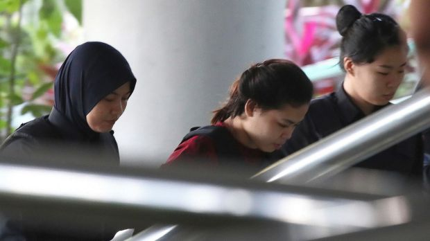 Indonesian Siti Aisyah, center, is escorted by police as she arrives in court in Kuala Lumpur.