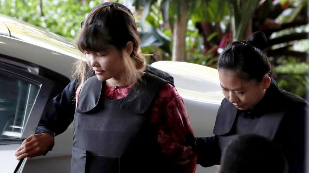 Vietnamese Doan Thi Huong, left, is escorted by police as she arrives in court in Kuala Lumpur.