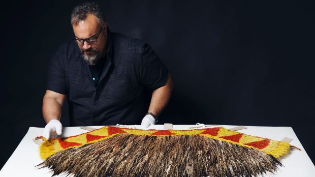 Logan Metcalfe, collections officer Pacific at the Australian Museum, examines the feathers of the rare cape given to ...