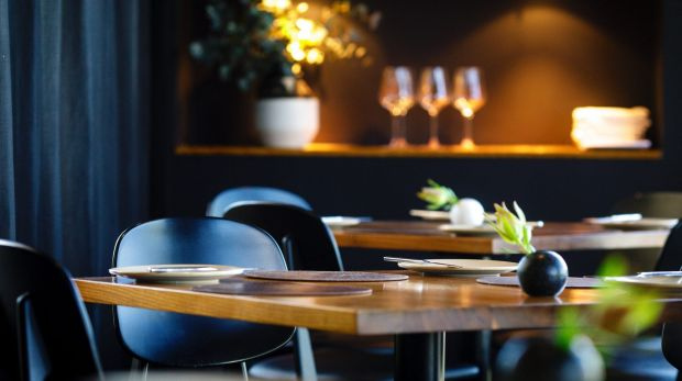 The dining room has long sheer black curtains, dark carpet, black-clad wait staff, leather placemats on the tables - ...