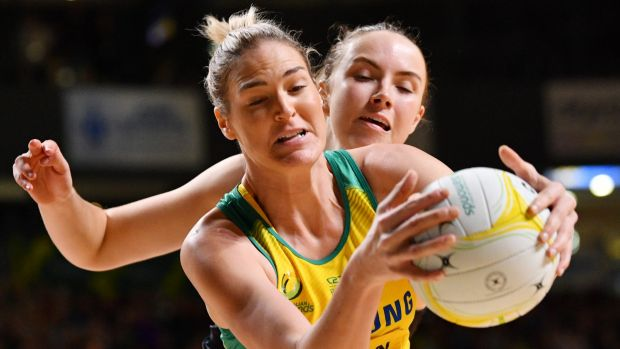 Australian goal shooter Caitlin Bassett holds off Silver Fern defender Kelly Jury in Adelaide on Wednesday night.