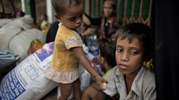 Two-year-old Noyem Fatima offers a piece of banana to her brother Yosar Hossein, 7, in Leda, Bangladesh. Hossein carried ...