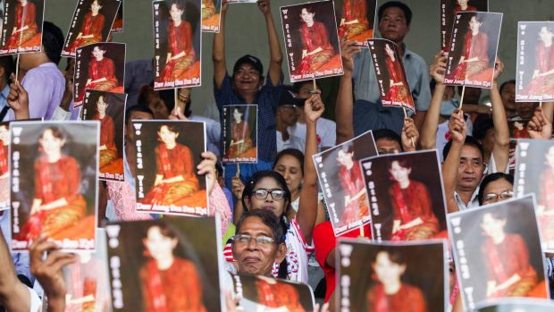 Supporters of Myanmar's ruling National League for Democracy (NLD) raise portraits of its leader Aung San Suu Kyi during ...