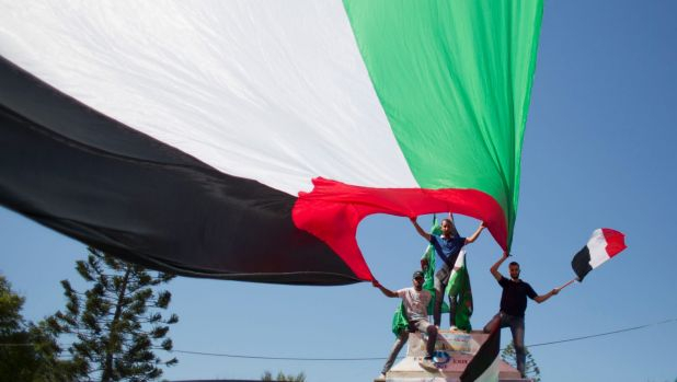 Palestinians wave national and Egyptian flags to celebrate the reconciliation agreement.