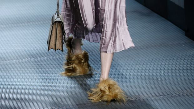 In this Wednesday, January 5, 2015 file photo, a model wears footwear with wisps of fur as part of the Gucci women's ...