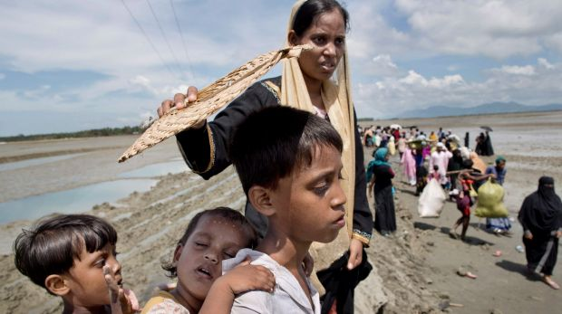 Foriza Begum holds a fan to shield her son Yosar Hossein, 7, and daughter Noyem Fatima, 2, on their way to a Bangladesh ...