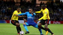 Arsenal's Alexandre Lacazette, center, battles for the ball with Watford's Abdoulaye Doucoure, right, and Christian ...