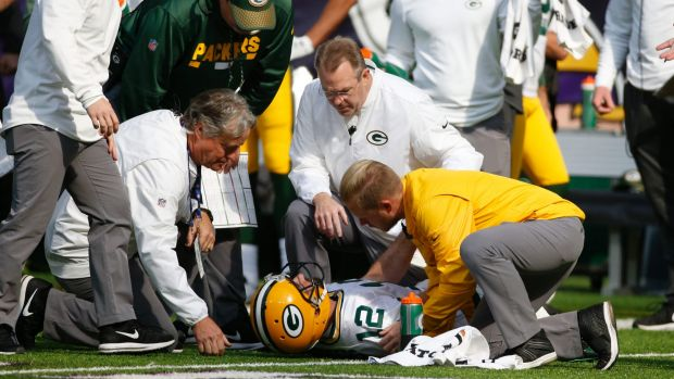 Green Bay Packers quarterback Aaron Rodgers is attended to by medical staff.