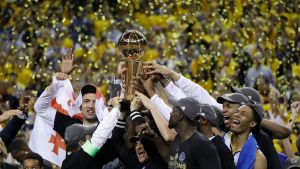 Golden State Warriors players, coaches and owners hold up the Larry O'Brien NBA Championship Trophy after game 5 of ...