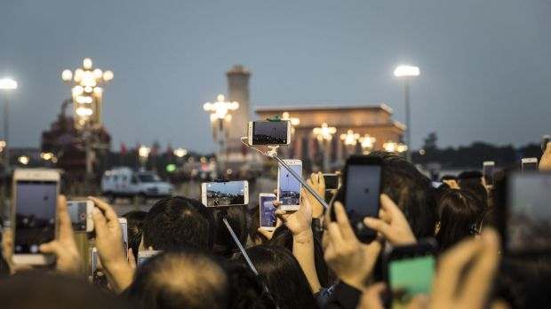 Visitors use smartphones to take photographs and videos of a flag lowering ceremony at Tiananmen Square on Monday.