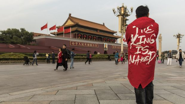 Tourists and pedestrians walk past a portrait of former Chinese leader Mao Zedong at Tiananmen Square in Beijing.