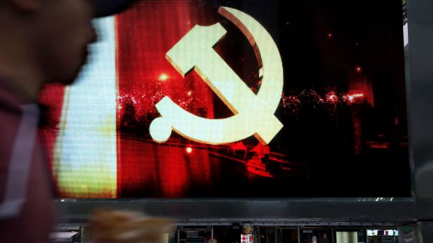 A man walks by digital display showing the Communist Party logo in Shanghai, China, on Saturday.