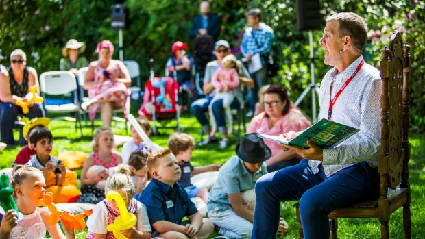 On the lawns of the Prime Minister's Lodge in Canberra, Rhys Muldoon reads to children at an event run by a charity ...
