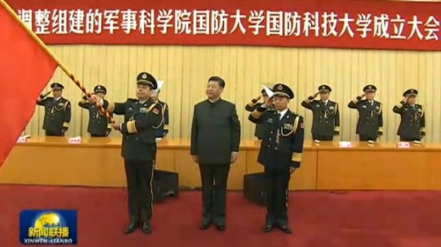 General Yang stands next to Chinese President Xi Jinping holding the PLA flag.