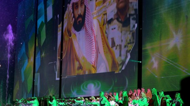 Saudi men perform under a giant screen showing an image of Saudi Crown Prince Mohammed bin Salman during National Day ...
