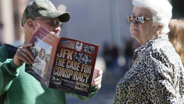 A vender shows a woman a magazine during her visit to Dealey Plaza in Dallas, Texas.