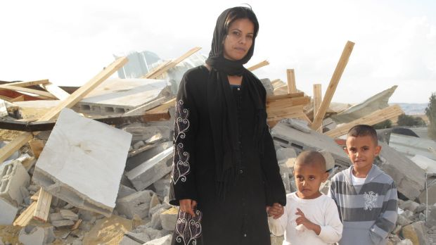 Rifa al-Oqbi and her sons stand in front of their demolished home in the Bedouin village of al-Qrain in November 2011.