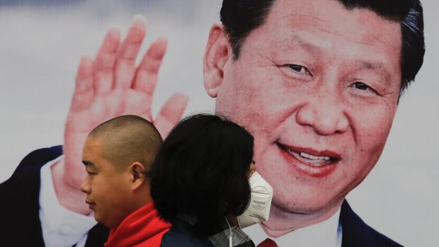 A masked woman and a man walk by a poster of Chinese President Xi Jinping on a street in Beijing.