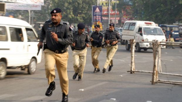 Police run to take up positions outside the Federal Investigation Agency in Lahore