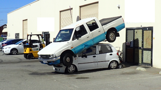 The ute was stacked on top of the car using a forklift, damaging both vehicles.