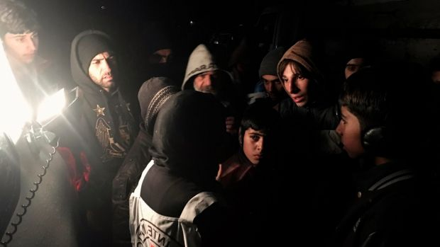 The head of the Red Cross delegation in Syria, Marianne Gasser, speaks to residents as they gather around an aid convoy.