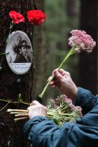 A woman places flowers at a memorial in Levashovo Cemetery that is the resting place of victims of Stalin's Great Terror.