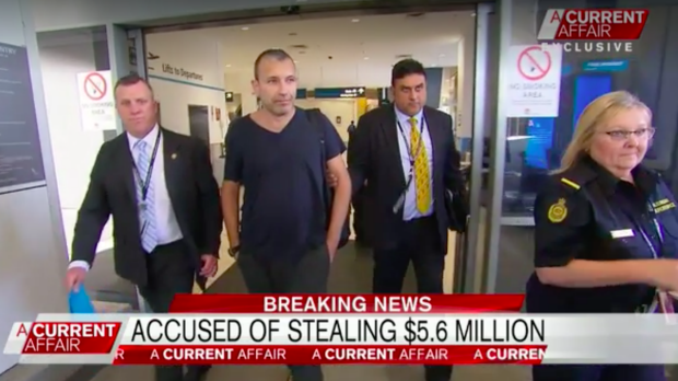 Detectives escort Daniel Albert through Sydney Airport.