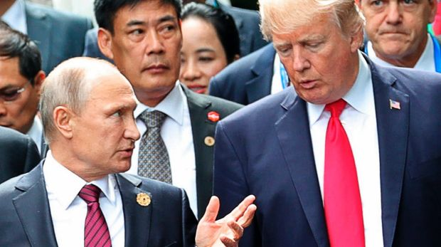 US President Donald Trump and Russia's President Vladimir Putin talk during a photo session at the APEC Summit in ...