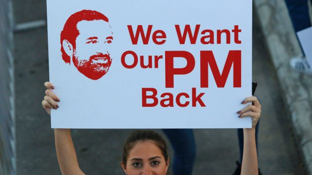 A Lebanese woman holds a placard supporting the outgoing Lebanese Prime Minister Saad Hariri to return from Saudi Arabia ...