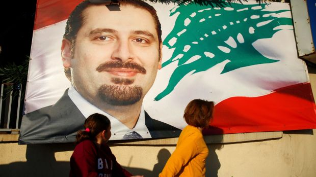 A woman and her daughter pass by a poster of outgoing Prime Minister Saad Hariri, in Beirut, Lebanon.