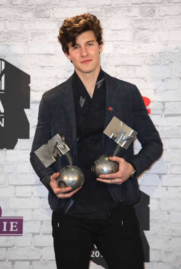 Singer Shawn Mendes poses for photographers with his awards for Best Song and Best Artist backstage.