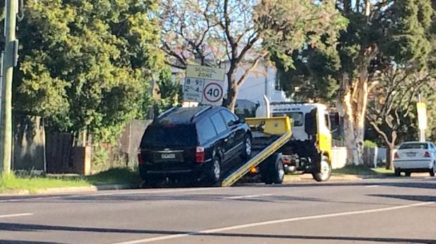 A tow truck arrived just before 6.20pm and the black Kia minivan was loaded onto the tray of the truck before it was ...