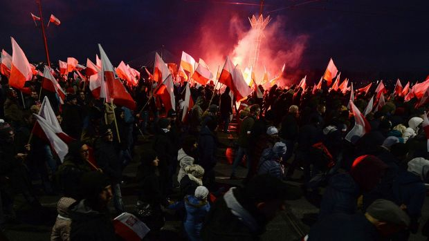 Demonstrators burn flares and wave Polish flags during the annual march to commemorate Poland's National Independence ...