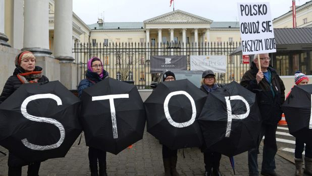 A group of civic rights activists stand in front of the City Hall in Warsaw as they protest what they saw as the ...