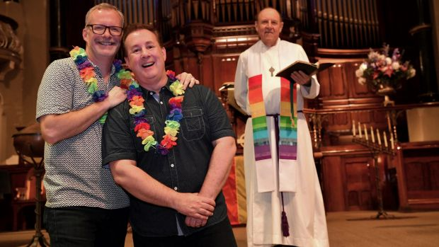 Reverend Ric Holland of St Michael's in Collins Street, with couple Matthew Jones, left, and Jonathon Welch, has called ...