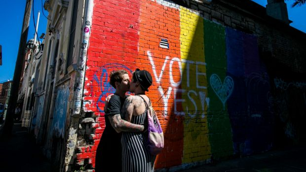 """A couple embrace to celebrate the """"yes"""" verdict of Australia's postal vote on same-sex marriage in Newtown."""