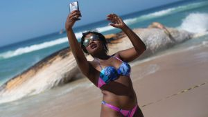 A woman poses for a selfie in front of the carcass of a humpback whale on Ipanema beach, in Rio de Janeiro.