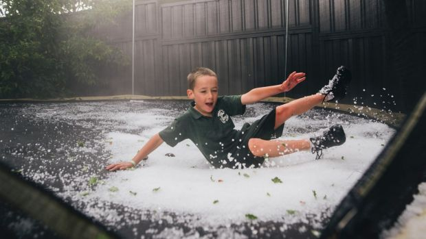 Campbell Ashcroft, 6, of Yarralumla, playing in the hail on his backyard trampoline.