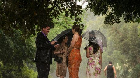 Visitors to the Tan walking track open their brollies and shelter under trees as the rain hits.