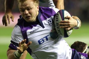 Fiery Scots: Luke Hamilton is brought down after charging into the All Blacks defence.