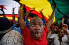 A happy protester pulls a face as he and others stand under a large national flag, at a demonstration of tens of ...