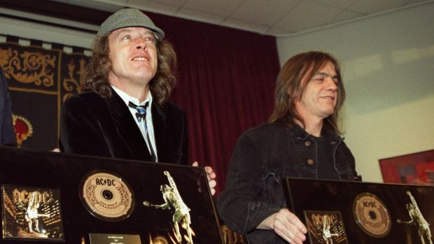Malcolm Young (right) and fellow AC/DC founder and brother Angus Young pose with a presentation for their album Stiff ...